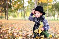Mały śliczny dżentelmen w czarnym kapeluszu w jesień parku Zdjęcie Stock
