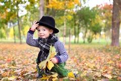 Mały śliczny dżentelmen w czarnym kapeluszu w jesień parku Fotografia Stock