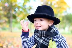 Mały śliczny dżentelmen w czarnym kapeluszu w jesień parku Zdjęcie Royalty Free