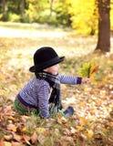 Mały śliczny dżentelmen w czarnym kapeluszu w jesień parku Zdjęcia Stock