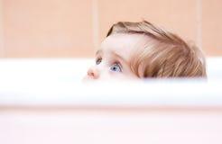 Mały śliczny dziecka zerkanie z skąpania Obraz Stock