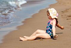 Mały śliczny dziecko dziewczyny obsiadanie na morze plaży zdjęcie stock