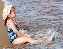Mały śliczny dziecko dziewczyny obsiadanie na morze plaży obraz stock