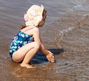 Mały śliczny dziecko dziewczyny obsiadanie na morze plaży zdjęcia royalty free