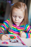 Mały śliczny dziewczyna obraz z ołówkami podczas gdy Fotografia Royalty Free