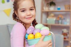 Mały śliczny dziewczyny Easter świętowania pojęcia mienia wiadro z jajkami w domu obraz stock