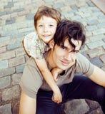 Mały śliczny syn z nowożytnym dojrzałym modnisia ojcem w miasta szczęśliwym uśmiechniętym przytuleniu, stylu życia pojęcia ludzie Fotografia Stock