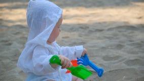 Mały śliczny szczęśliwy dziecko bawić się z piaskiem i na plaży zbiory wideo