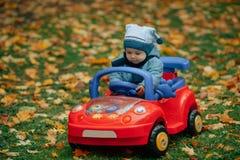 Mały śmieszny chłopiec jeżdżenia zabawki samochód obraz royalty free