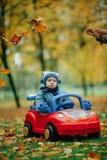 Mały śmieszny chłopiec jeżdżenia zabawki samochód fotografia stock