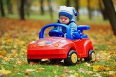 Mały śmieszny chłopiec jeżdżenia zabawki samochód obraz stock