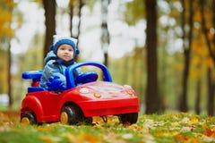 Mały śmieszny chłopiec jeżdżenia zabawki samochód obrazy royalty free