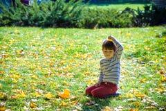 Mały śmieszny chłopiec obsiadanie na trawie z gumową kaczką na jego głowie obrazy stock