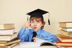 Mały śmieszny profesor w akademickim kapeluszu z rarytasu piórem wśród starych książek Obraz Stock
