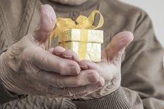 Mały żółty prezent na marszczącej palmie starsza osoba Obrazy Stock