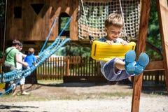 Mały arywista bierze linowego most Chłopiec zabawa czas, dzieciaka pięcie na pogodnym ciepłym letnim dniu Fotografia Stock