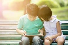 Mały Asianboy i dziewczyna bawić się wraz z komputerem ta Zdjęcia Royalty Free