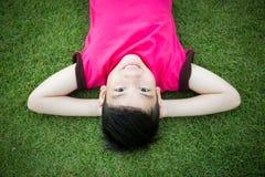 Mały Azjatycki dziecko kłaść w dół na trawie Obrazy Royalty Free