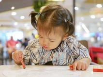 Mały Azjatycki dziewczynka uczenie chwycić kredkę i robić malować sama zdjęcia stock