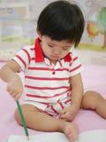 Mały Azjatycki dziewczynka uczenie trzymać rysunek na książce i ołówek Obrazy Royalty Free