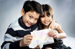 Mały azjatykci chłopiec i dziewczyny mienia obrazka wiith słowo Fotografia Royalty Free