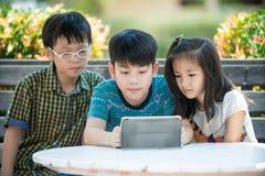 Mały azjatykci dziewczyny i chłopiec obsiadanie na długim drewnianym krześle używa cyfrę Fotografia Stock
