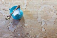 Mały błękitny ceramiczny miotacz owsa mleko z drewnianą łyżką balansował przez wierzchołek fotografia stock