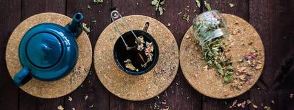 Mały błękitny teapot, kubek herbata, i suszymy ziołowej herbaty na drewnianym tle jako depresji wydajny ziołowy hypericum właśnie zdjęcia royalty free