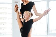 Mały baleriny rozciąganie iść na piechotę z jej nauczycielem w baletniczym studiu obraz stock