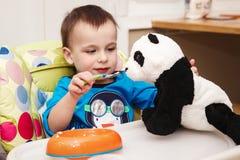Mały berbeć chłopiec łasowania posiłek, karmi zabawkę obraz royalty free