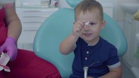 Mały beztroski chłopiec obsiadanie w krześle Śliczna chłopiec bawić się z stomatologicznym wszczepem ?e?ska profesjonalista lekar zbiory wideo