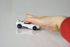 Mały biel zabawki samochód, pchający dziecka ` s ręką Ręka jest defo obraz stock