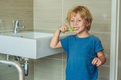 Mały blond chłopiec uczenie szczotkuje jego zęby w domowym skąpaniu K Zdjęcia Stock