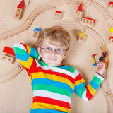Mały blond dziecko bawić się z drewnianymi linia kolejowa pociągami salowymi Zdjęcia Royalty Free