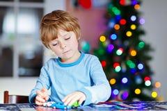 Mały blond dziecko bawić się z samochodami i zabawkami w domu obraz stock
