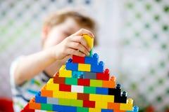 Mały blond dziecko bawić się z udziałami kolorowi plastikowi bloki Urocza preschool dzieciak chłopiec jest ubranym kolorową koszu obraz royalty free