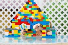 Mały blond dziecko bawić się z udziałami kolorowi plastikowi bloki Urocza preschool dzieciak chłopiec jest ubranym kolorową koszu fotografia stock