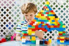 Mały blond dziecko bawić się z udziałami kolorowi plastikowi bloki Urocza preschool dzieciak chłopiec jest ubranym kolorową koszu zdjęcie royalty free