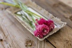 Mały bukiet różowy ranunculus kwiatu lying on the beach na rocznik tacy Zdjęcie Royalty Free