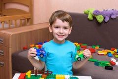 Mały caucasian dziecko bawić się z udziałami kolorowy klingeryt blokuje salowego Żartuje chłopiec jest ubranym koszula i ma zabaw Zdjęcia Royalty Free