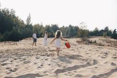 Mały caucasian dziewczyna bieg wzdłuż plaży w biel sukni z czerwonym wiadrem widok z powrotem obraz royalty free