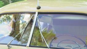 Mały chłopiec jedzie trwanie retro samochodowe sztuki wokoło na kamerze Chłopiec w retro nakrętka siedzi w zbiory