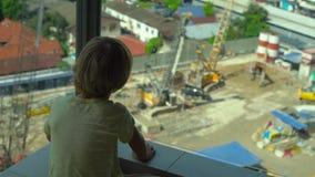 Mały chłopiec obsiadanie na balkonie z szklanymi ścianami ogląda budowę kondygnacja budynek zbiory