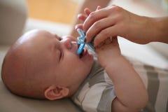 Mały chłopiec płacz i jej macierzysty daje pacyfikator obraz royalty free