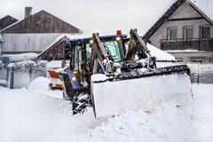 Mały ciągnik z lemieszem usuwa śnieg ładuje podczas ciężkiej śnieżyca klęski, wioska domy w tle obraz stock