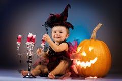 Mały czarownicy dziewczyny dziecko śmia się wśród bani i świeczek Obraz Stock