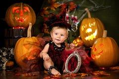 Mały czarownicy dziewczyny dziecko śmia się wśród bani i świeczek Obrazy Stock