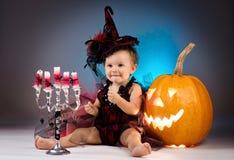Mały czarownicy dziewczyny dziecko śmia się wśród bani i świeczek Zdjęcie Stock