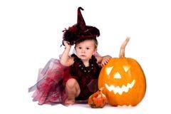 Mały czarownicy dziewczyny dziecko śmia się wśród bani i świeczek na białym tle Zdjęcia Stock