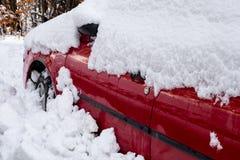 Mały czerwony samochód zakrywający stapianie śniegiem w opóźnionej zimie zdjęcie royalty free